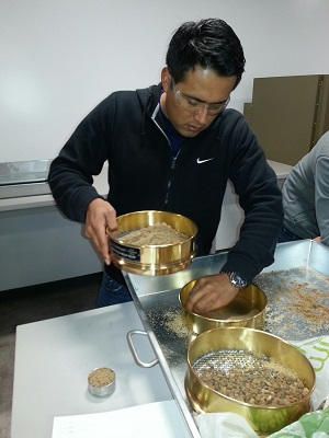 A student uses sieves in soil mechanics